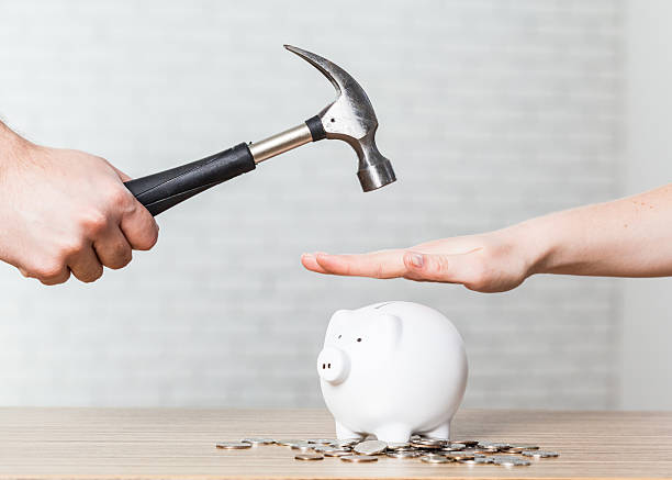 hammer raised above a white piggy bank stock photo