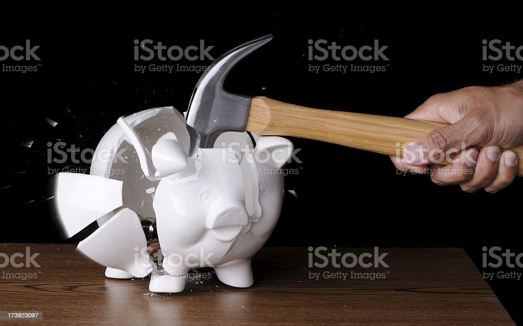 Hammer Smashing Piggybank Full of Coins stock photo