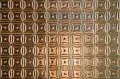 Hammered tin tile ceiling background with a repeating design.