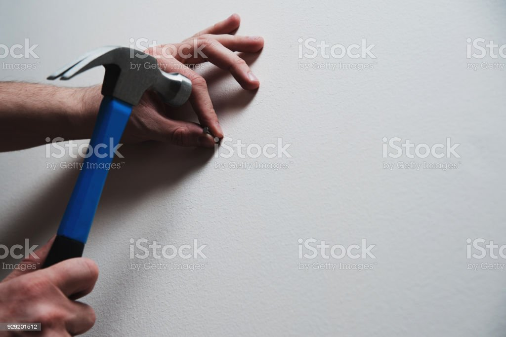 Hammering a nail into the wall. stock photo