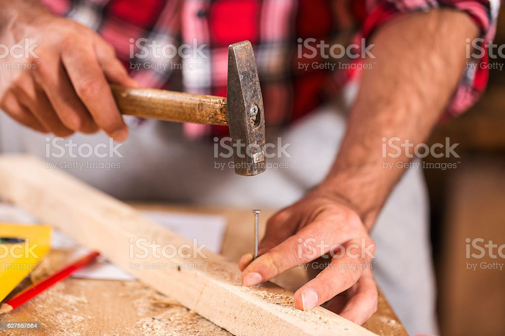 Hammering a nail into wooden board. Close up stock photo