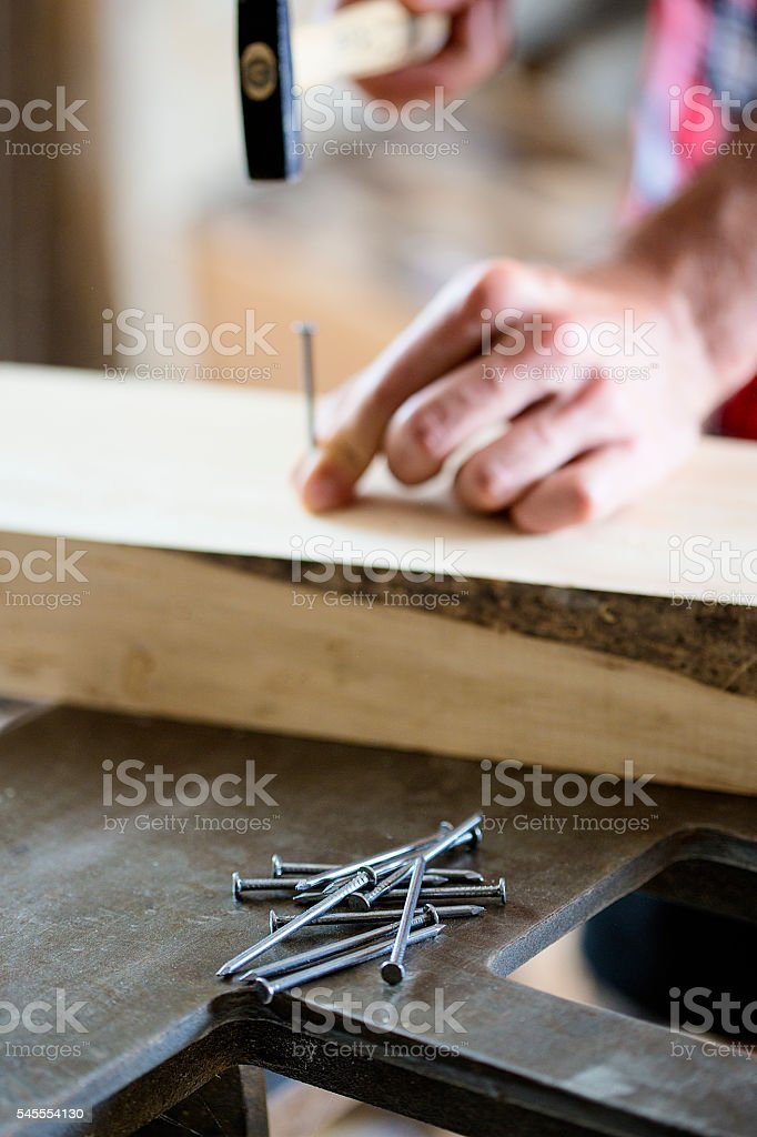 Hammering a nail into wooden board stock photo