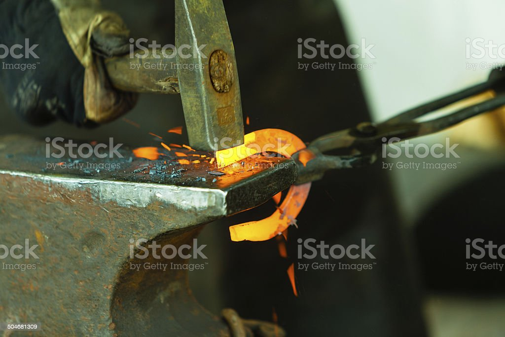 Hammering glowing steel stock photo