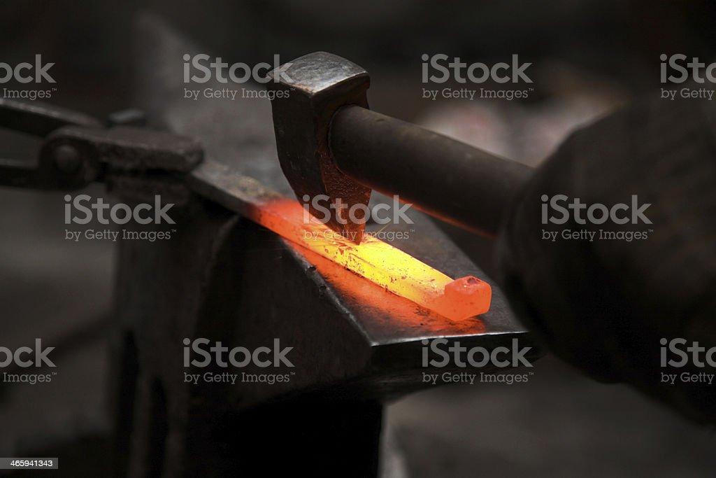 hammering hot iron in blacksmith workshop stock photo