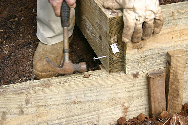 Hammering Large Nail into Wooden Garden Wall stock photo