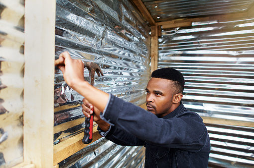 An African man with a hammer in a sink shack building a shack in Kayamandi Stellenbosch Cape Town South Africa