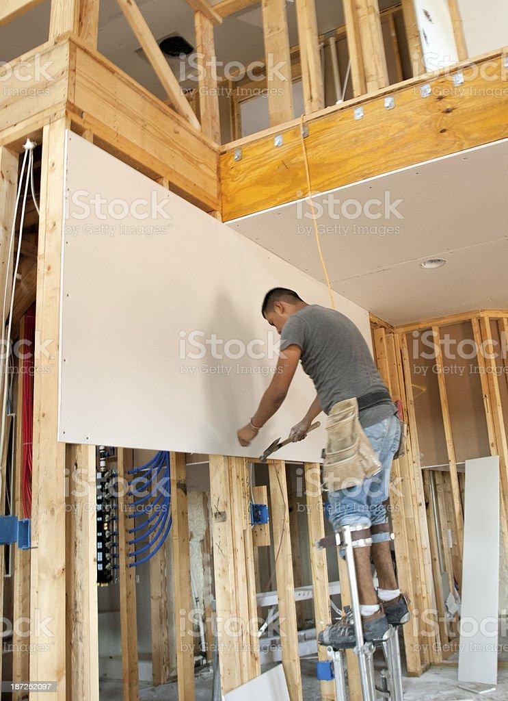 Hammering Nails into the Sheetrock stock photo