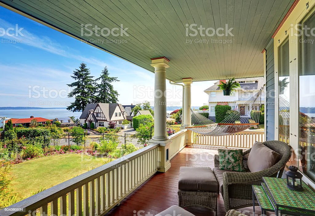 Hammock and patio area with armchairs at wooden walkout porch stock photo