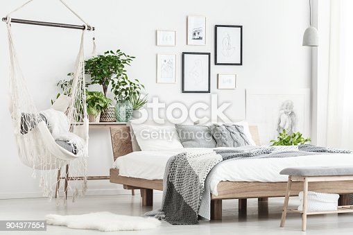 Patterned bedding on king-size bed and hammock above white fur in simple bedroom with posters