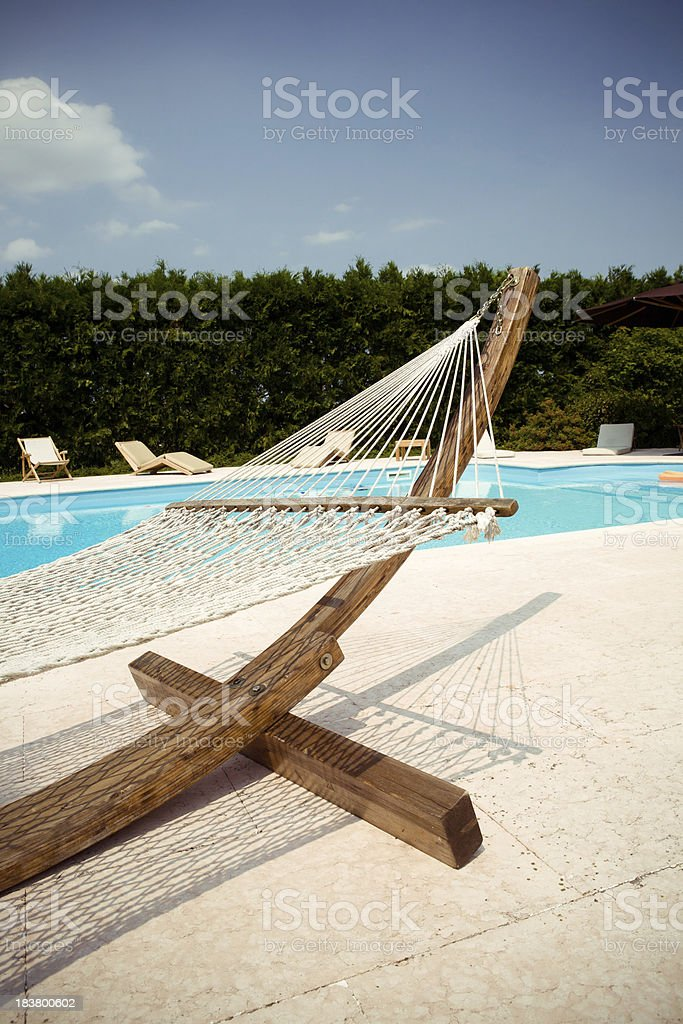 Hammock on the edge of a swimming pool stock photo