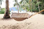 Hammock anchored between palm trees on a sandy beach, El Nido, Palawan island, Philippines