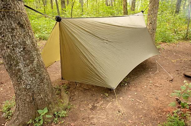 hammock tarp hanging in woods - planenzelt stock-fotos und bilder
