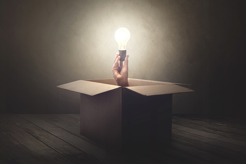 istock han holding light bulb coming out from a paper box 978249810