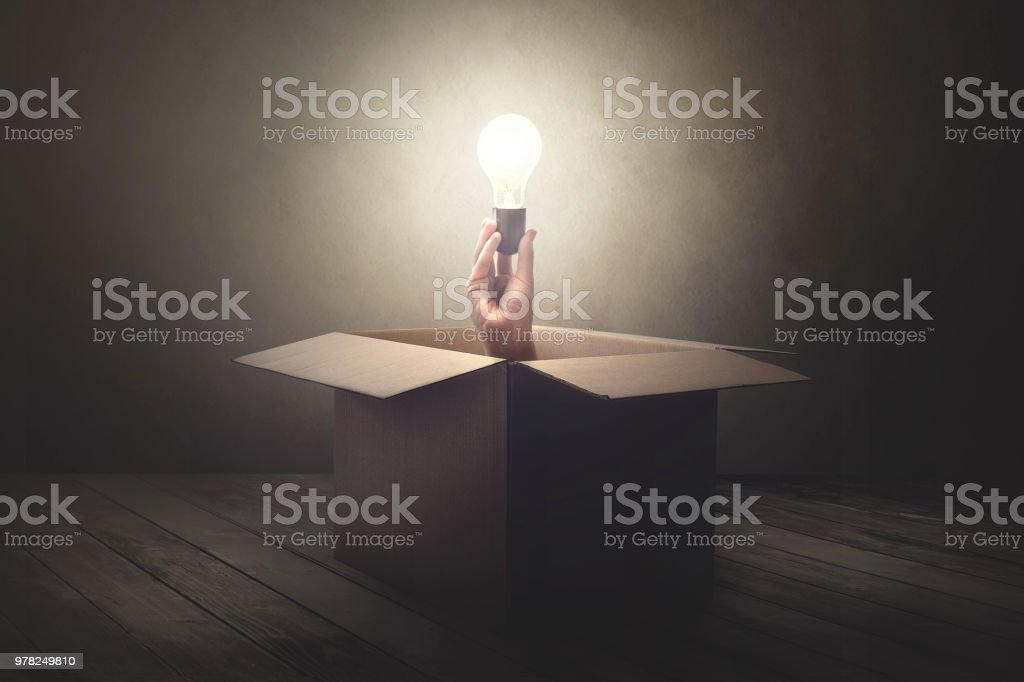 han holding light bulb coming out from a paper box stock photo