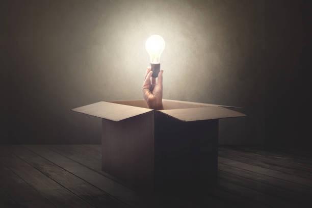 han-holding-glühbirne, die sich aus einer pappschachtel - boxen live stock-fotos und bilder