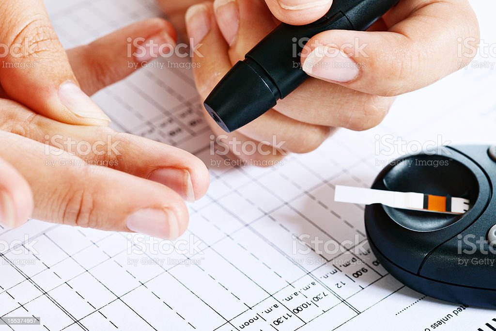 Hand about to draw blood with automated lancet stock photo
