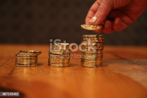 istock Hand adding ccoin change pile 667245452