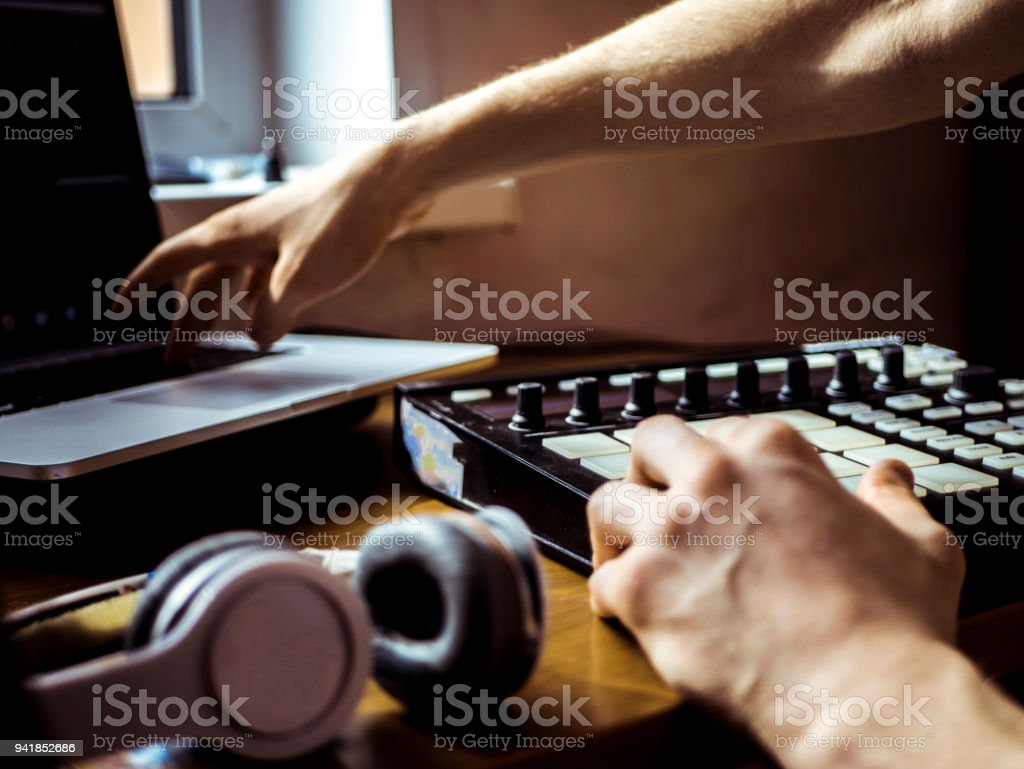 hand adjusting and controlling music on a laptop stock photo