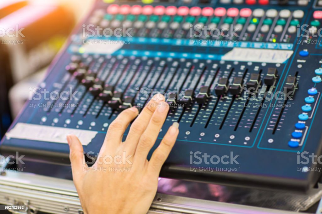 Hand adjusting audio mixer. sound engineer hands working on sound...