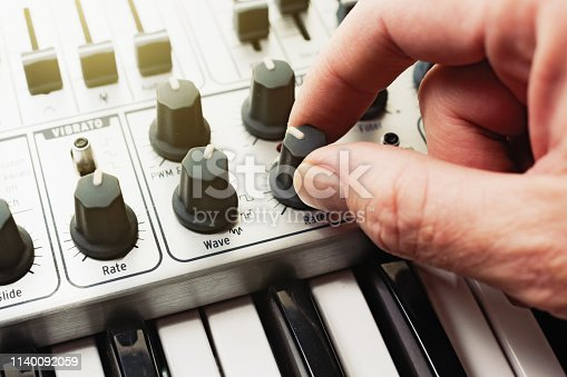 A hand turns a control knob on a retro-style analog synthesizer, seen in close-up with part of the keyboard visible beneath. Black and white shot.