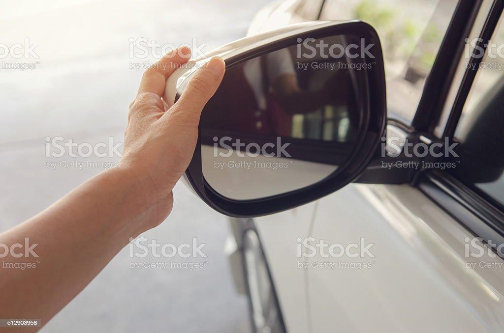 Mão ajustando lado de espelho retrovisor. - foto de acervo
