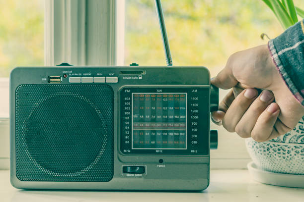 hand adjusting the settings of vintage old radio, search for radio station wave f hand adjusting the settings of vintage old radio, search for radio station wave wide receiver athlete stock pictures, royalty-free photos & images