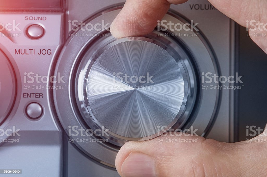 Hand adjusting volume control. Technology concept. stock photo