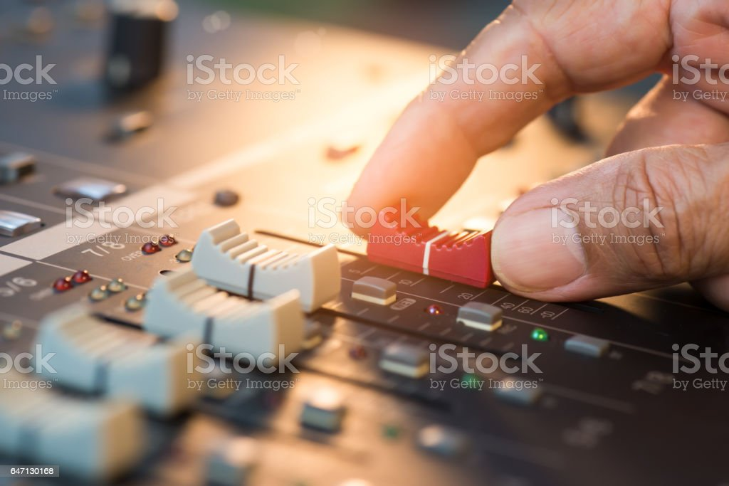 Hand adjusting volume fader of digital audio mixer. Professional sound engineer balancing volume of audio inputs in concert,bokeh background stock photo