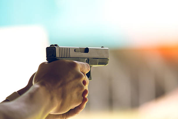 hand aim pistol in academy shooting range - foto de stock