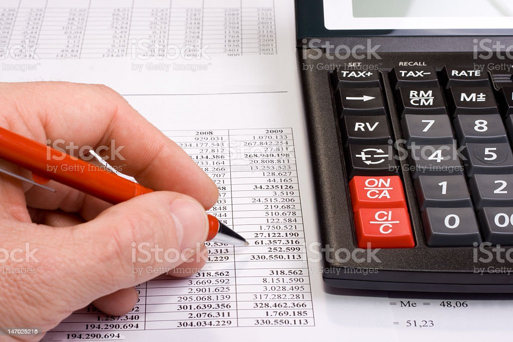 A hand analyzing a financial data table using a calculator royalty-free stock photo