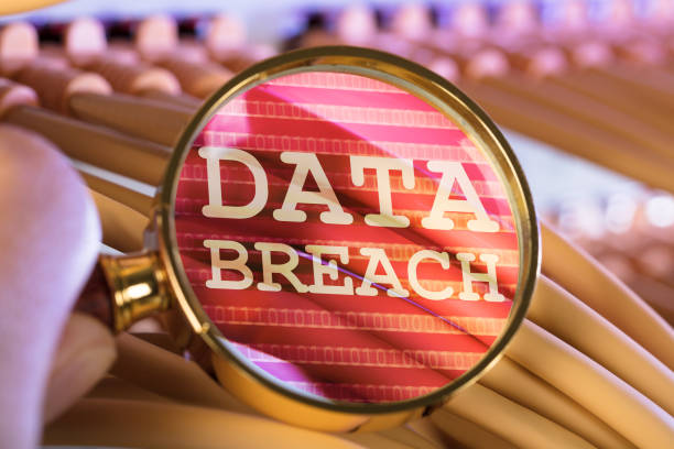 Hand Analyzing Data Breach Through Magnifying Glass Over Cables stock photo