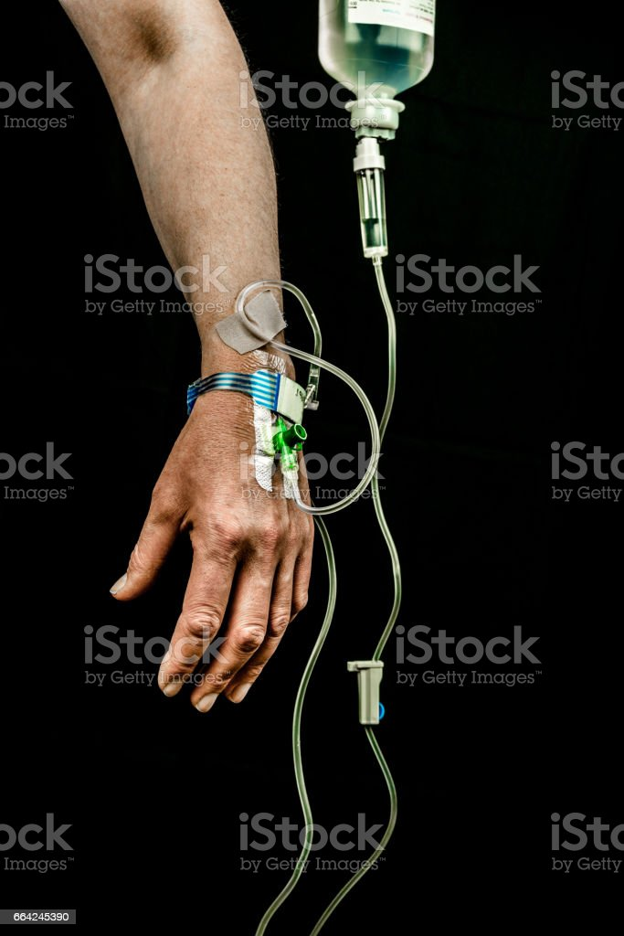 Hand and arm of patient with iv fluid treatment on black background, vertical. stock photo
