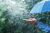 istock Hand and blue umbrella under heavy rain against nature background. Rainy weather concept. 1162332653