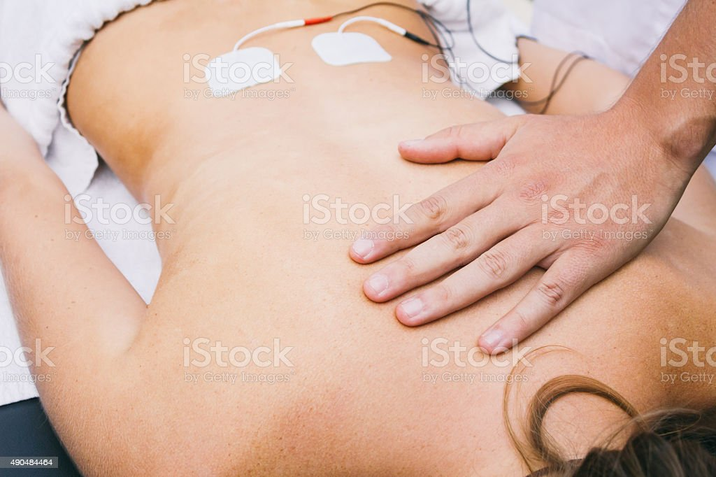 Hand and electrodes on a patient's lumbar stock photo