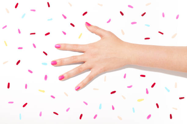 Hand and multi colored nail polish swathes flat lay stock photo