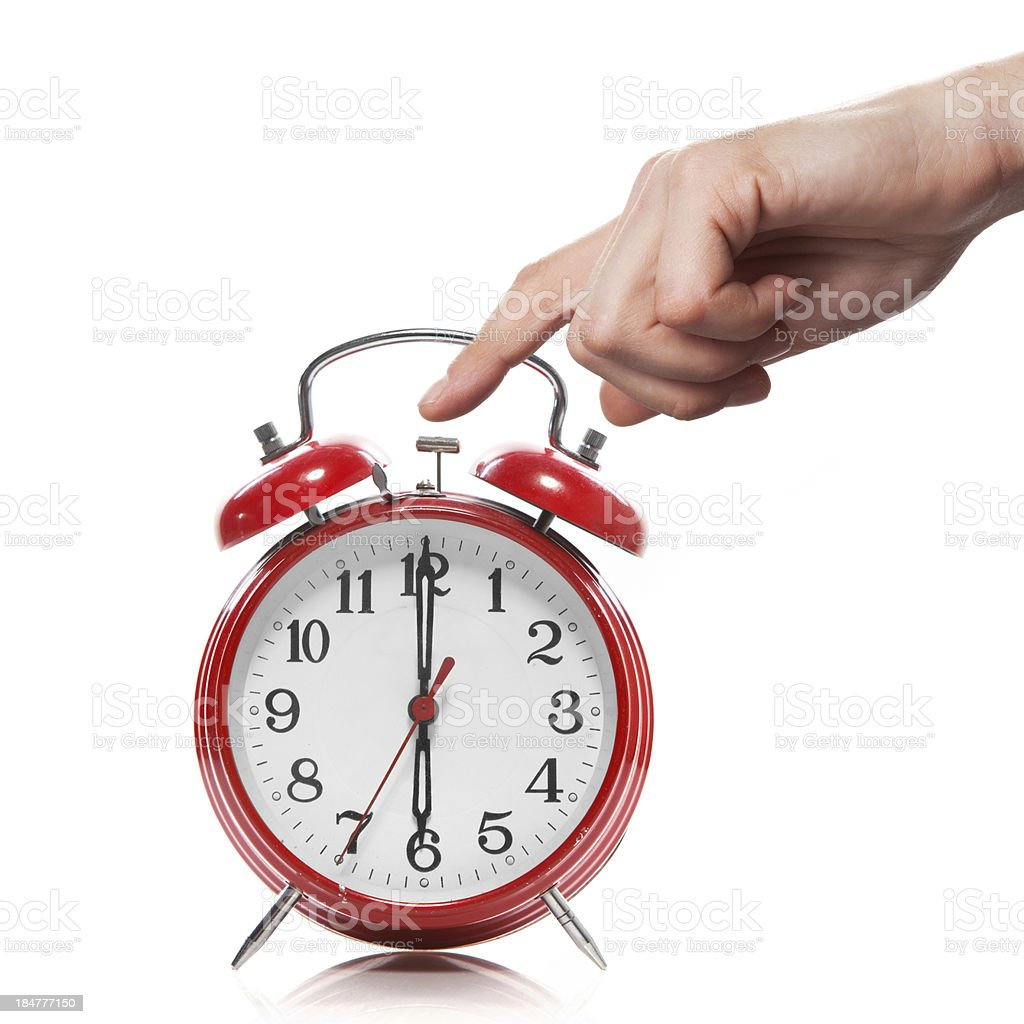 hand and red old style alarm clock isolated on white stock photo