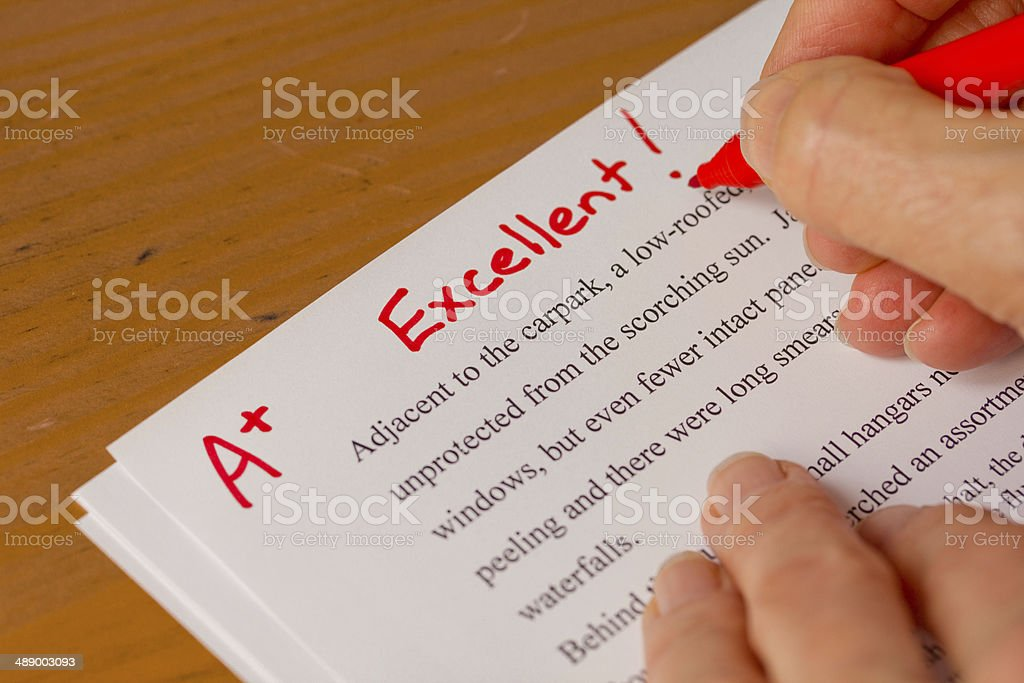 Hand and Red Pen Grading Papers with Excellent stock photo