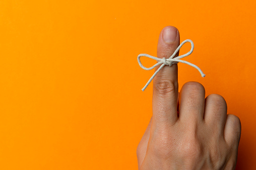 Hand and string tied on index finger on orange background.