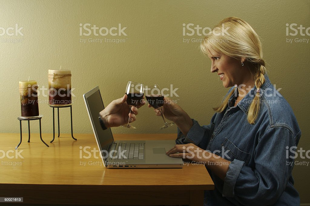 Hand and Wine Glass Coming Through Laptop Screen royalty-free stock photo