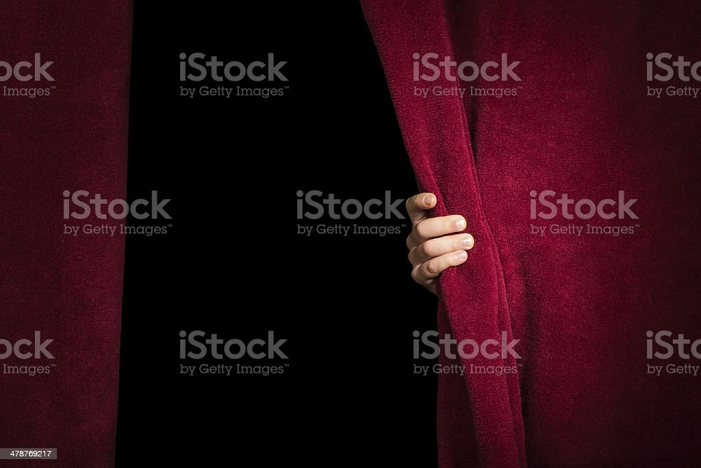 Hand appearing beneath the curtain. stock photo