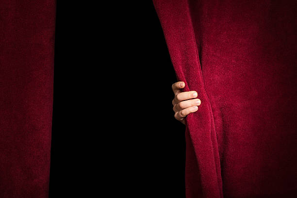 hand appearing beneath the curtain. - curtain stock photos and pictures