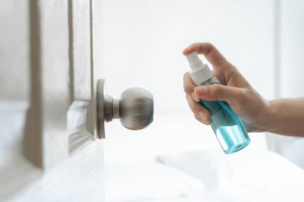 Aplicación manual de alcohol spray a la puerta, dormitorio de la perilla de la puerta para proteger el coronavirus. - foto de stock