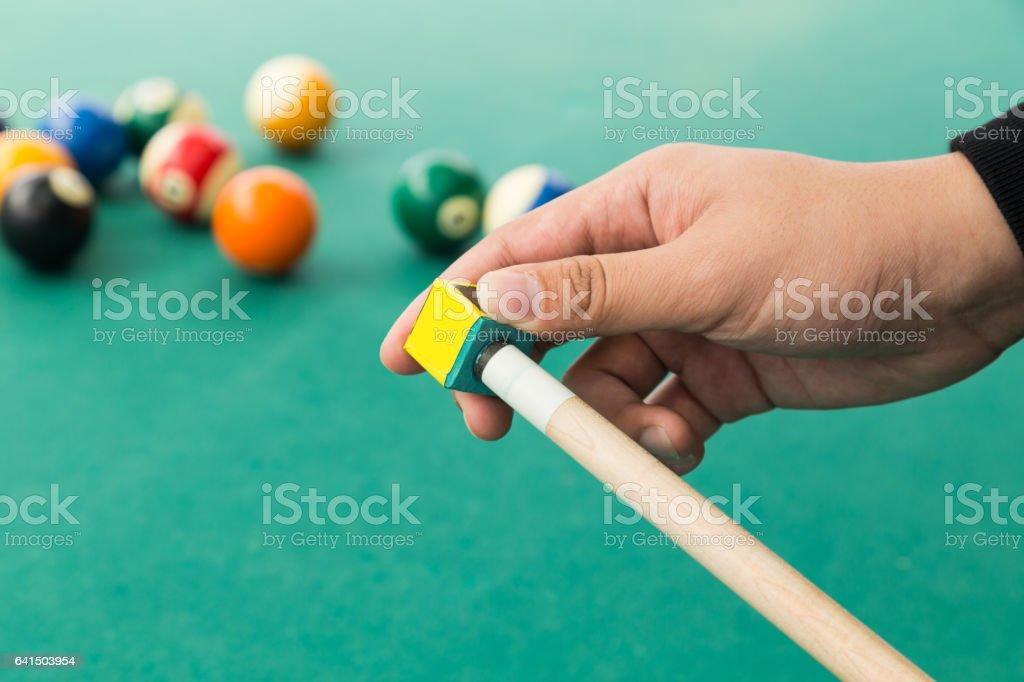 Hand applying chalk on tip of billards pool stick stock photo
