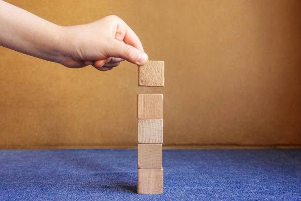 Hand arranging five wood blocks stacking on top with wooden table. Business concept for growth success process stock photo