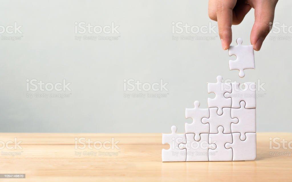 Hand, die Vermittlung von Jigsaw Puzzle Stapeln als Schritt Treppe auf Holztisch. Business-Konzept für Erfolg Wachstumsprozess – Foto