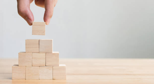 mão que arranja o bloco de madeira que empilhe como a escada. conceito do negócio para o processo do sucesso do crescimento - bloco - fotografias e filmes do acervo