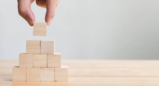 手工排列木塊堆疊作為臺階樓梯。成長成功過程的商業理念 - 厚板 個照片及圖片檔