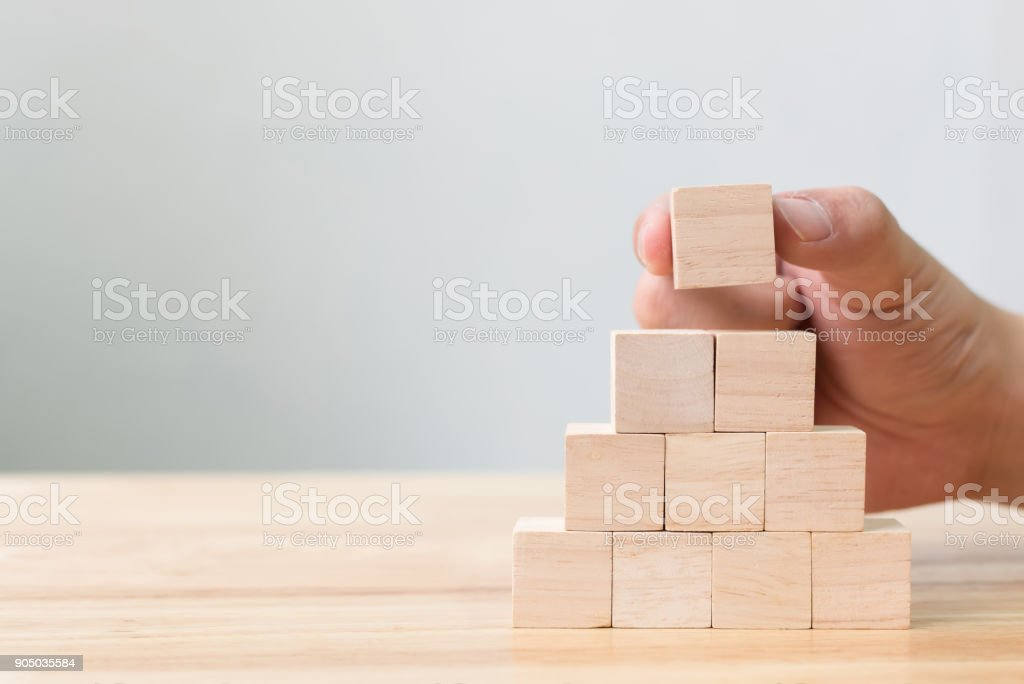 Hand arranging wood block stacking as step stair. Business concept for growth success process stock photo