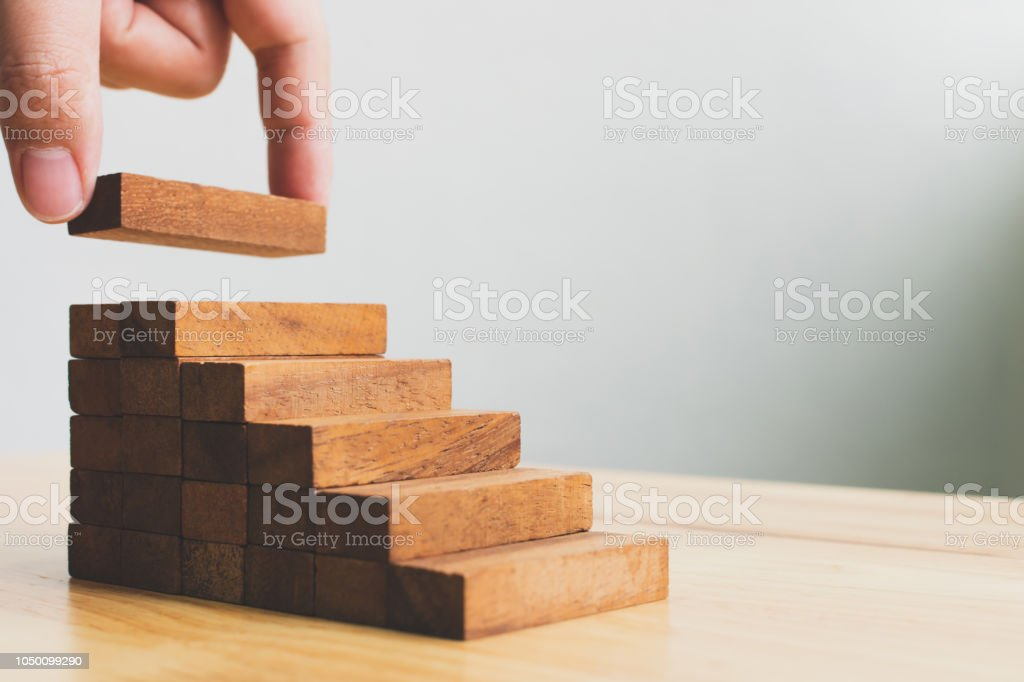 Hand arranging wood block stacking as step stair. Ladder career path concept for business growth success process foto stock royalty-free