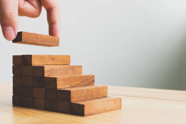 hand schikken hout blok stapelen als stap trap. ladder carrière pad concept voor groei succes bedrijfsproces - zelf ontwikkeling stockfoto's en -beelden